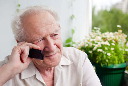 pensive senior man speaking on the phone with somebody Stock Photo
