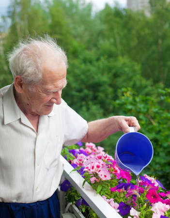 smiling senior man watering the flowers on his balcony photo