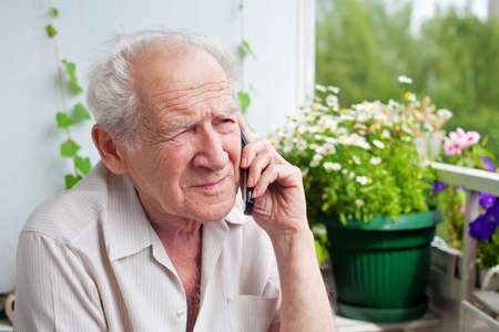 only one senior adult man: sad, gloomy senior man speaking on the phone with somebody