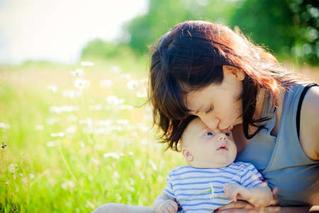 young mother kissing her little son on a field of camomile photo