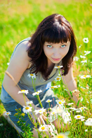 beautiful dark-haired smiling woman sitting on a grass, smelling camomiles photo