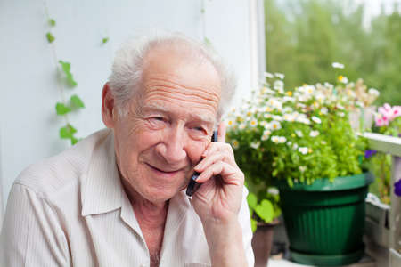 smiling senior man speaking on the phone with somebody photo