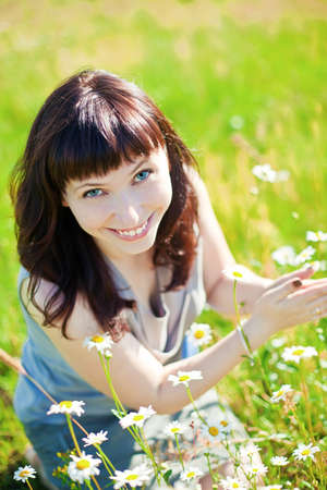 beautiful dark-haired smiling woman sitting on a grass among chamomile Stock Photo - 19357679