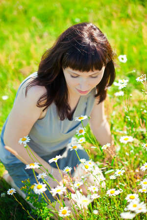 beautiful dark-haired woman sitting on a grass, admiring camomile photo