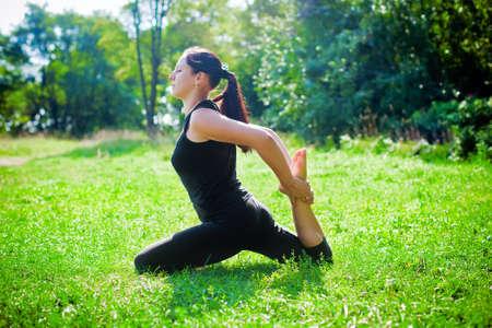aerobic treatment: woman in black making yoga one-legged king pigeon pose