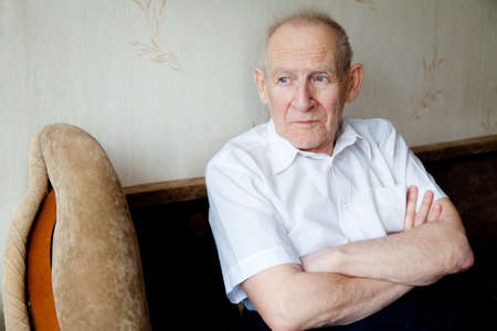 portrait of a pensive senior man with crossed arms, he is looking somewhere