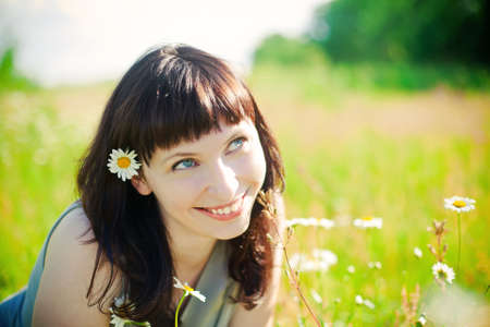beautiful young smiling woman lying on a grass among camomile photo
