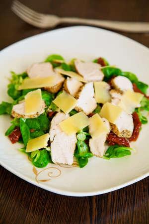 cornsalad: close-up fresh salad with cornsalad, baked chicken, dried tomatoes and parmesan Stock Photo