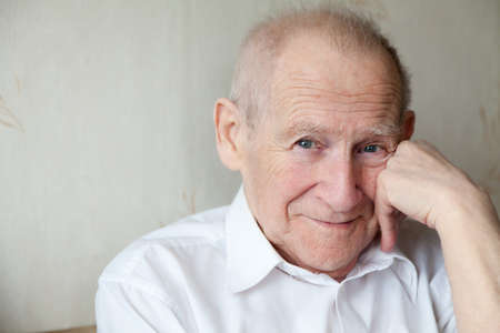 face portrait of a cheerful smiling senior man with his arm near his face