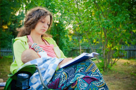mother breastfeeding her baby, seating on a chair outside and reading the book Stock Photo