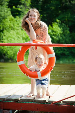 smiling woman and her little daughter posing with buoy photo