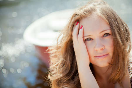 portrait of a beautiful young woman with water and boat background with copy-space photo