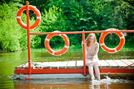 young woman wetting her feet in the river sitting on a platform photo