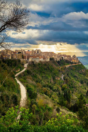 sun breaking through the clouds above the highest city in Sicily - Enna photo