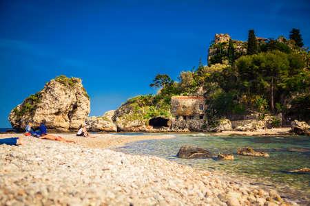 unrecognizable people: unrecognizable people acquiring a tan at the beach Isola Bella Editorial