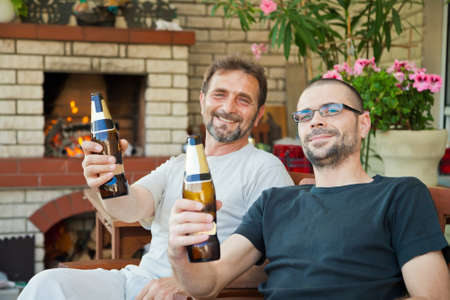 happy men are sitting in front of fireplace with beer bottles cheering and smiling Stockfoto