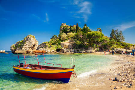 small boat for excursion in front of the island Isola Bella at Taormina, Sicily Foto de archivo