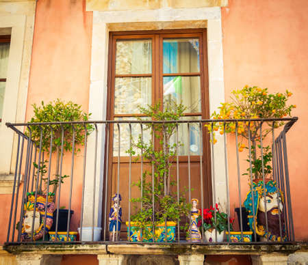 heads old building facade: Sicilian balcony with tangerine tree, ceramic figurines and vases