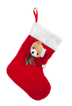 stocking cap: Christmas stocking with a teddy bear in a cap of Santa Claus on it, isolated on white