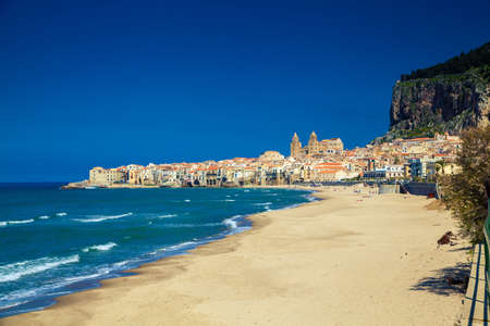 empty beach of Cefalu leading to its old town in a sunny spring day, Sicily