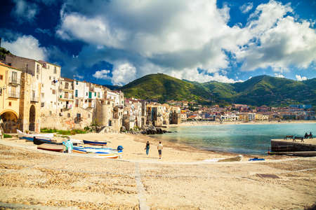 empty old beach of Cefalu with fishing boats in Sicily, Italy