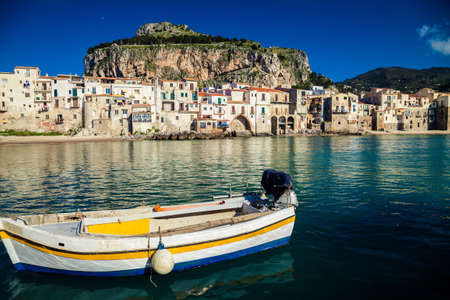 old boat drifting in a beautiful harbor at Cefalu Beach, Italy photo