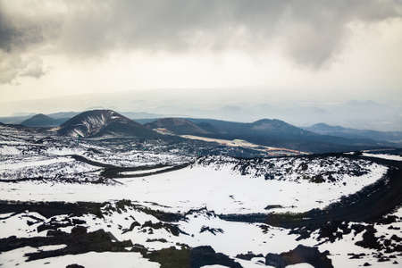 eruptive: view of the parking place and several extinct craters from one of the tops of volcano Etna in spring