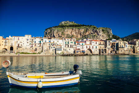 beautiful view of old boat drifting in a harbor at Cefalu Beach, Italy Stockfoto