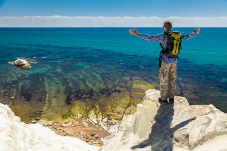 edge of cliff: man with opened arms standing on the edge of a cliff, enjoying amazing sea view