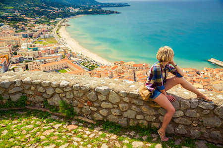 young woman sitting on the stone fence above town Cefalu in Sicily, enjoying beautiful top view Stockfoto