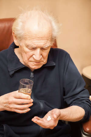 old man holding a glass of water and a mix of pills