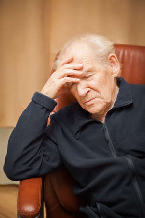 hand on forehead: old man with a headache, his hand on his forehead Stock Photo