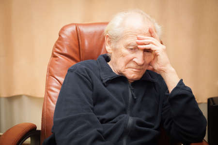 hand on forehead: sad old man with a hand on his forehead