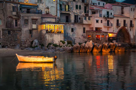 old boat drifting in a harbor of Cefalu at dusk, Sicily