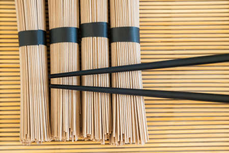 bundles: bundles of soba noodles and black chopsticks on bamboo background