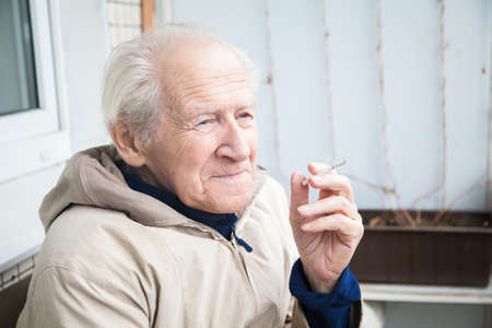 musing: thoughtful old man smoking a cigarette and musing upon a distant scene Stock Photo