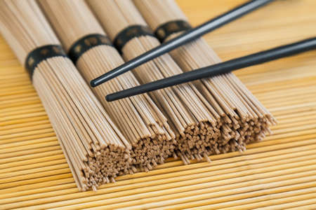 bundles: closeup bundles of soba noodles and black chopsticks on bamboo background