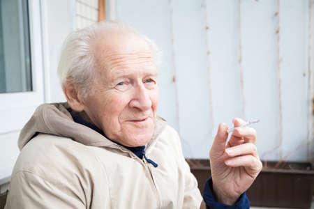 persona mayor: hombre sonriente de edad disfruta de un cigarrillo en el balcón