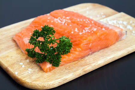 redfish: close-up raw salmon fillet with salt and parsley on a wood board