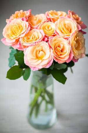 dainty: beautiful bouquet of dainty yellow-pink roses in a vase