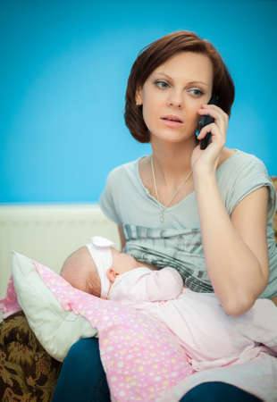 adult breastfeeding: adult woman breastfeeding her newborn daughter while speaking on the phone