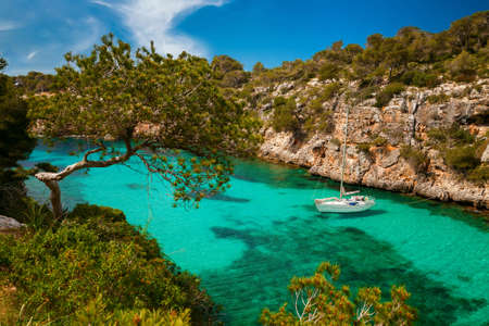 beaches of spain: small yacht floating in azure sea in the village Cala Pi, Majorca, Spain