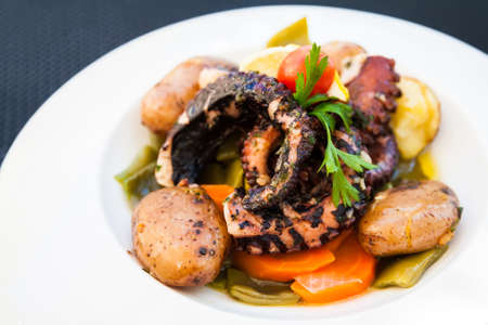 tentacle: grilled octopus tentacle served with potatoes and stewed vegetables Stock Photo