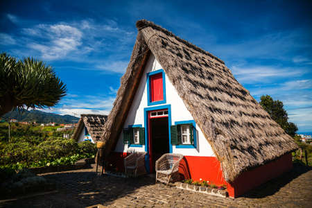 a house with a straw: traditional small-thatched triangular Madeira house, built of wood and thatched with straw