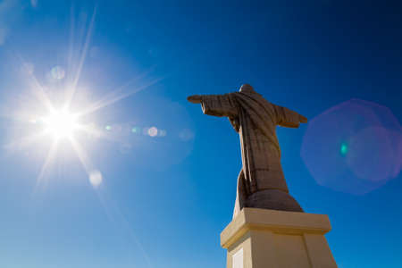 crist: the sun shining on the statue of Jesus Christ in Madeira, Portugal