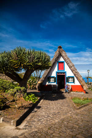 a house with a straw: traditional old triangular Madeira house, built of wood and thatched with straw