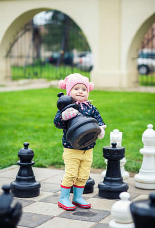 chessman: smart little girl taking a chessman while playing with giant chess outdoors