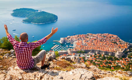 man with opened arms sitting on the edge of a cliff, looking down to the Old Town of Dubrovnik, Croatia Stockfoto
