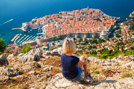 unrecognizable: unrecognizable woman looking at the Dubrovnik Old Town, sitting on the mountain above the city, Croatia Stock Photo