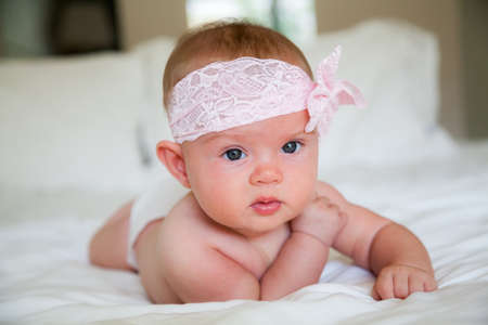 adorable baby girl with pink head bandage, lying on a belly